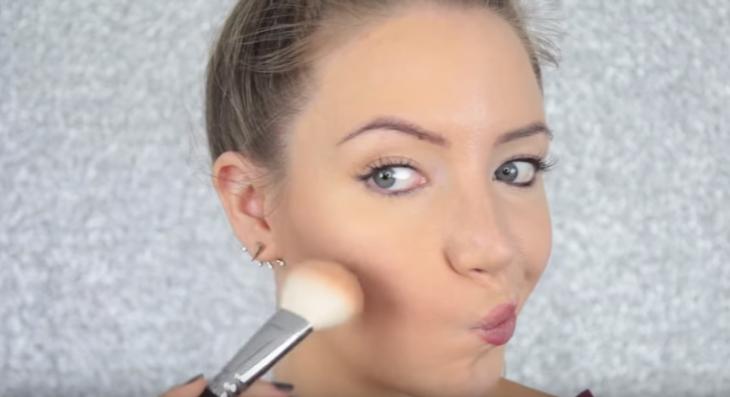 mujer aprieta la boca y se maquilla las mejillas