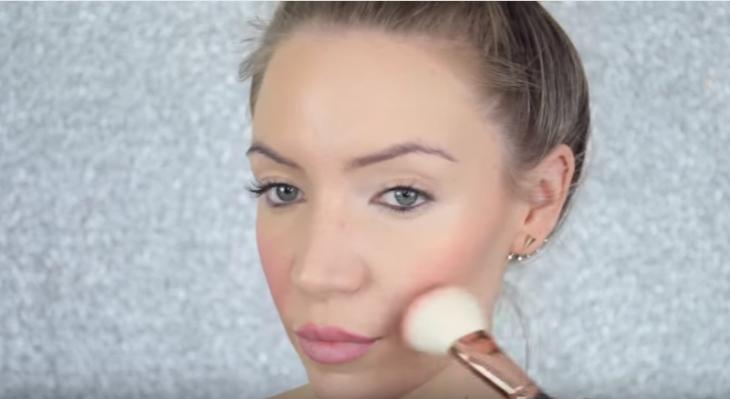 mujer maquillando sus mejillas con brocha