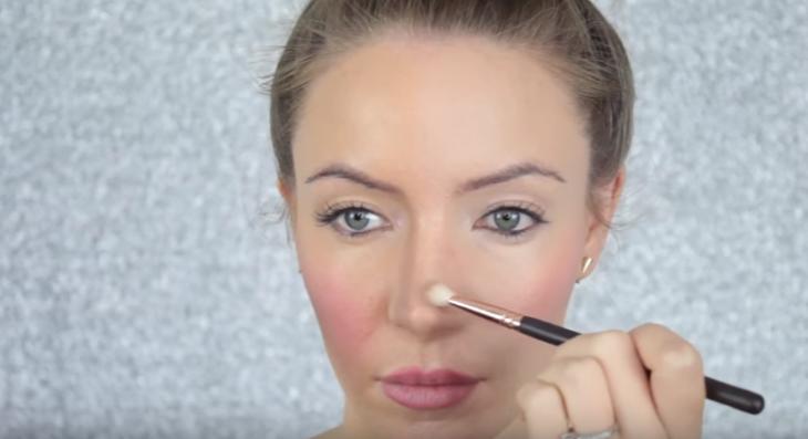 mujer rubia maquillando su nariz con brocha