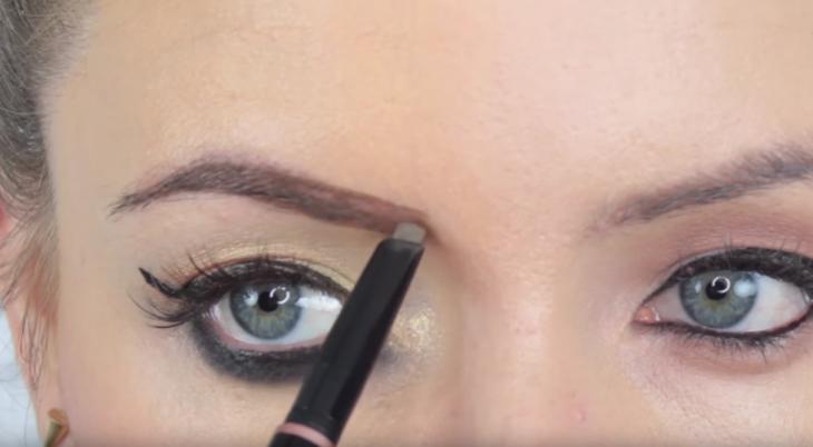 chica maquillando sus cejas con pincel