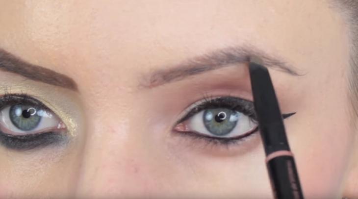 chica de ojos verdes maquillando cejas con pincel