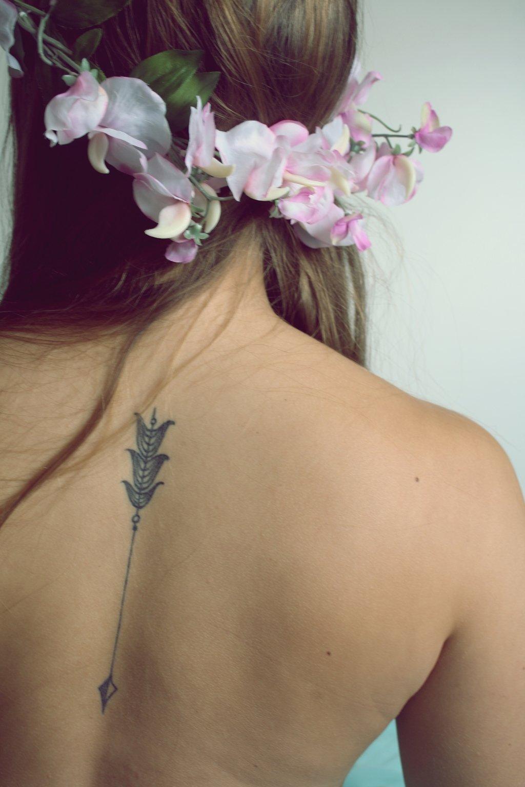 Tatuaje flecha en la espalda