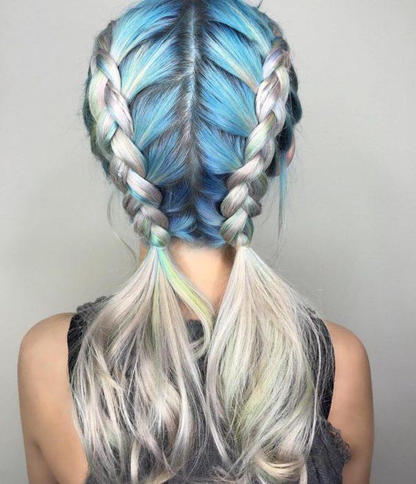 Chica luciendo un par de trenzas con su cabello azul y gris