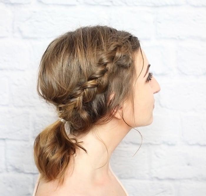 Chica luciendo una trenza que termina en una ponytall en la nuca
