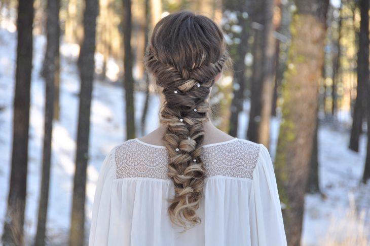 Chica luciendo una trenza con destellos de piedras en su cabello