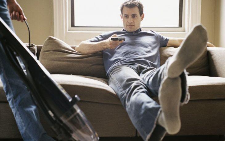 hombre sentado viendo TV mientras mujer aspira
