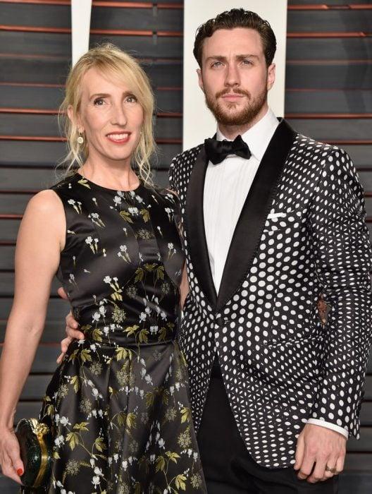 mujer rubia con vestido negro y hombre saco de puntos