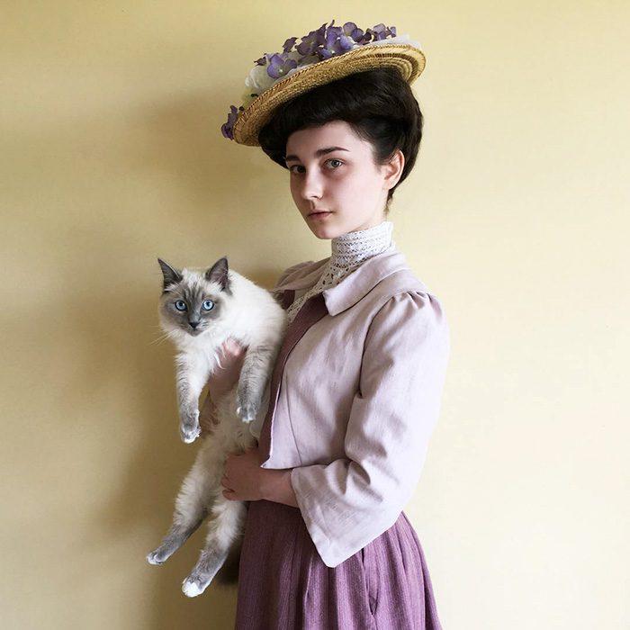 Chica usando un look clásico mientras sostiene a un gato