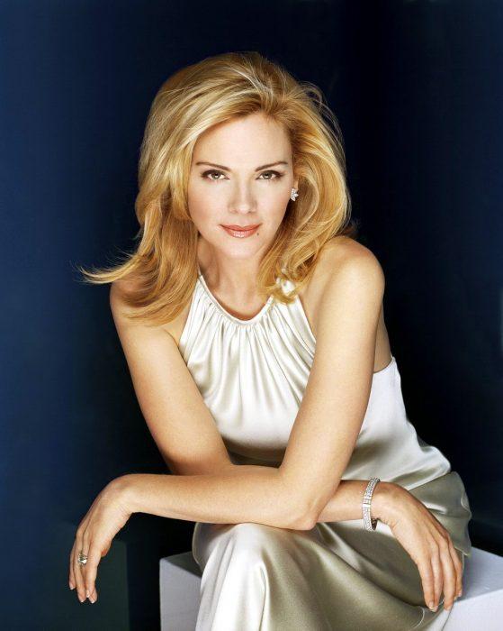 mujer rubia sentada con vestido blanco