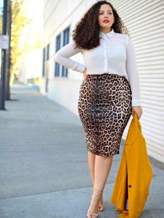 Chica curvy modelando una falda de leopardo y blusa blanca