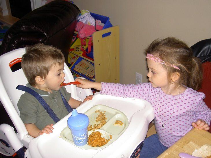 hermanita mayor dando de comer a hermano