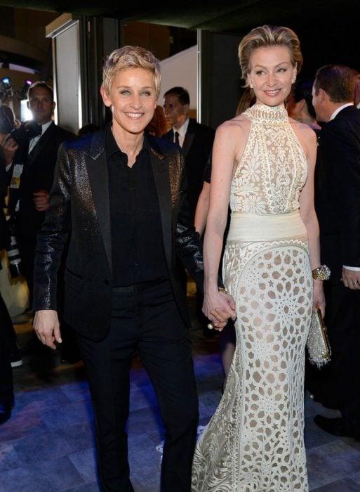 mujer rubia de saco negro y mujer de vestido blanco