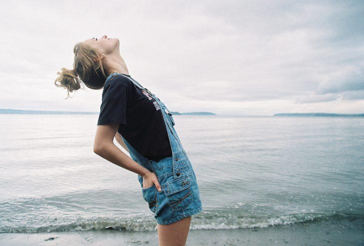 Chica mirando hacia el cielo frente al mar