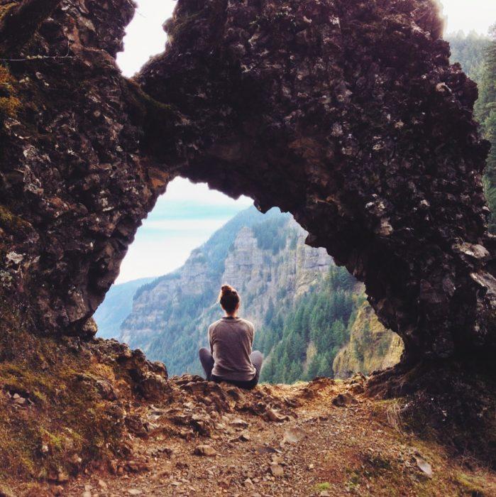 Chica sentada en el suelo de una montaña