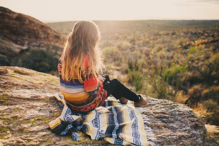 Chica sentada en una piedra mirando al horizonte