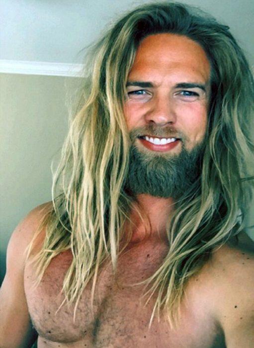 hombre rubio cabello largo con barba sonriendo
