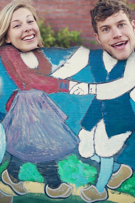 pareja sonriendo atras de pintura de pareja bailando