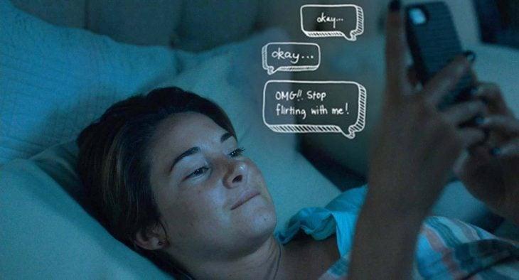 mujer con celular en la mano mandando mensajes de texto