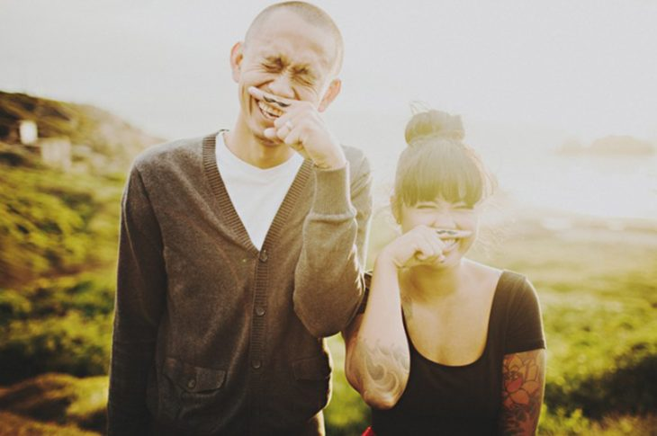 pareja sonriendo con dedos y bigotes hipster pintados
