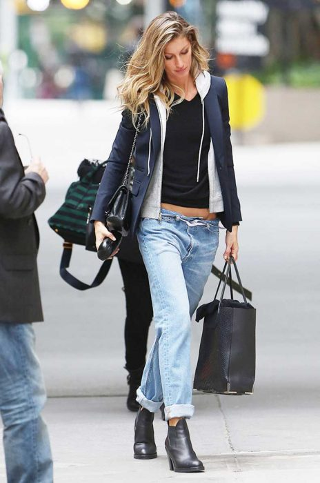 Chica usando hoddies y blazer en color gris con azul combinado con un pantalón de mezclilla mientras camina por la calle
