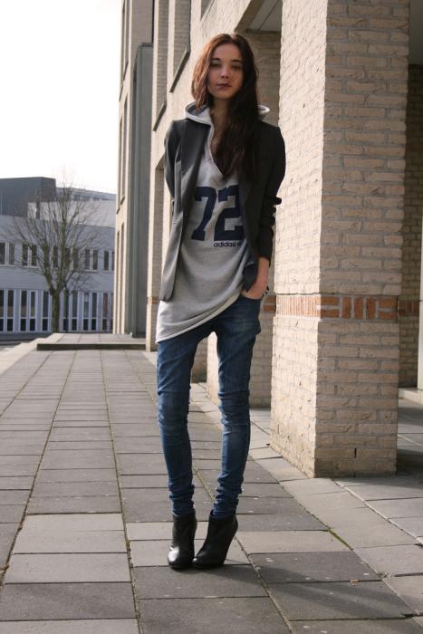 Chica usando hoddies y blazer largos mientras está parada en la calle