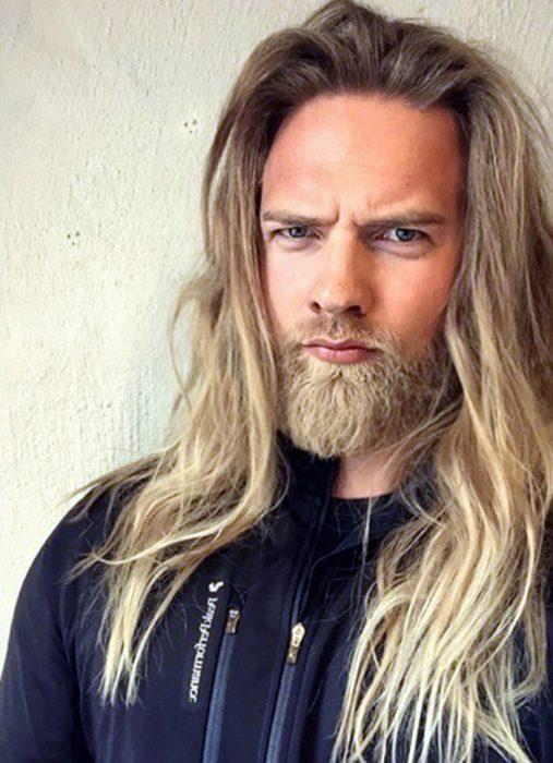 hombre de cabello rubio y largo con barba