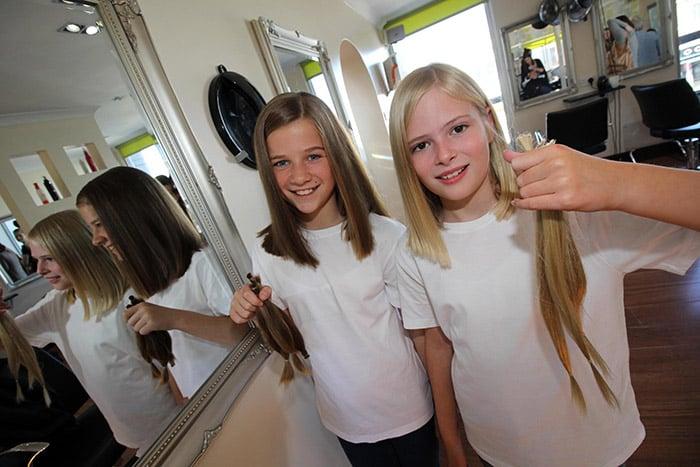 niñas cortandose el cabello para donarlo