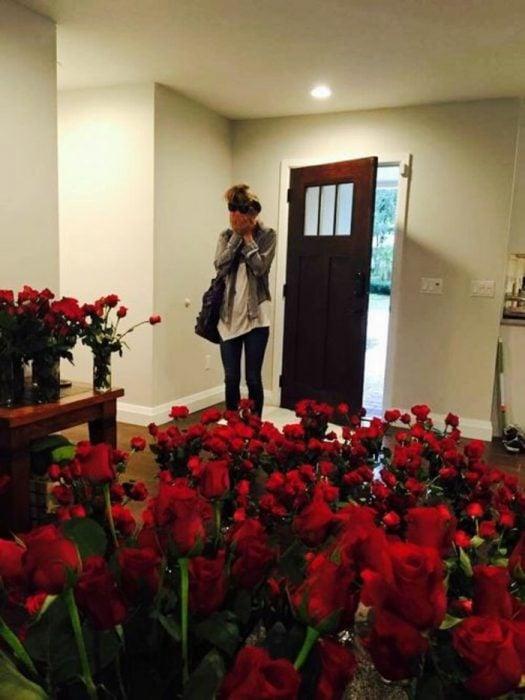 mujer sorprendida con rosas rojas en su casa