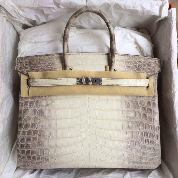 bolsa de mano de piel de cocodrilo en una caja