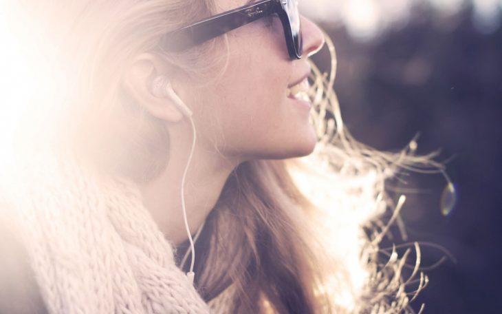 Mujer de perfil sonriendo y escuchando música con audífonos
