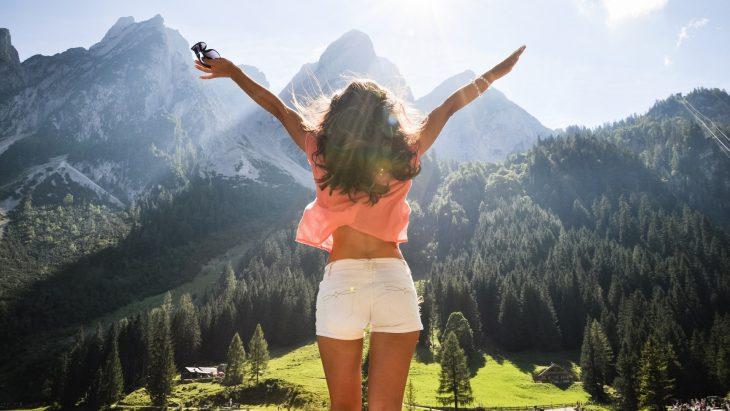 Mujer de espaldas con los brazos abiertos con un paisaje de montañas y árboles
