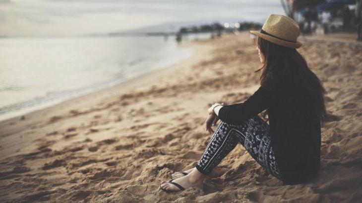 Mujer sentada en la arena viendo el atardecer en la playa