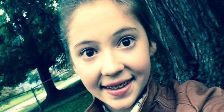 niña rubia con brackets sonríe