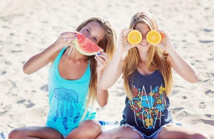 Chicas sentadas en la playa sosteniendo una sandia y una naranja
