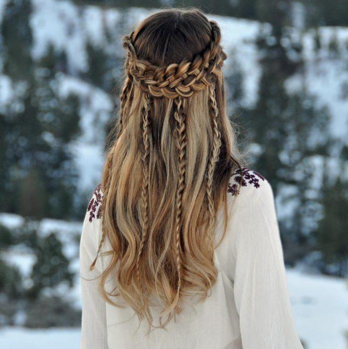 Chica en medio de la nieve luciendo una trenza en forma de corona sobre su cabeza