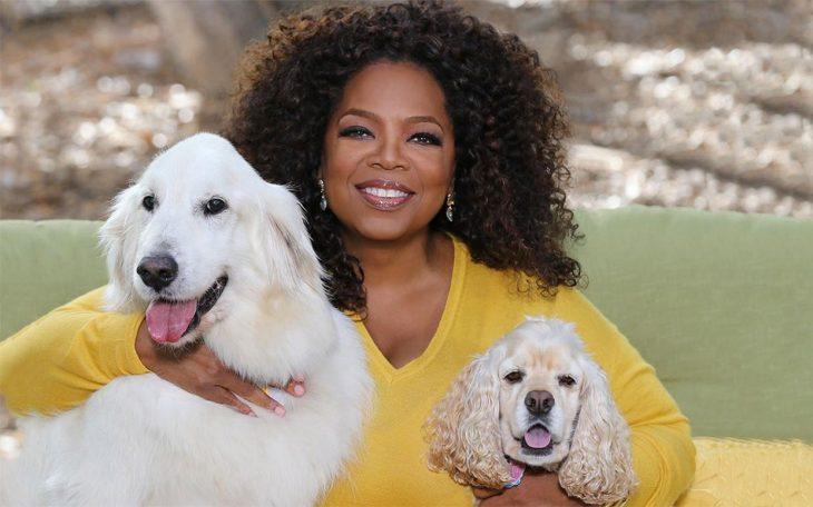 mujer morena sonriendo y abrazando a dos perros