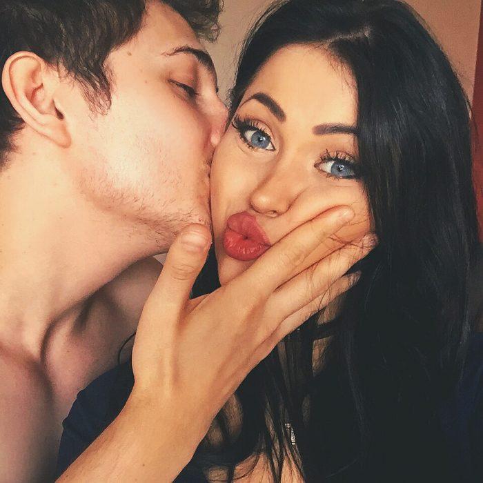hombre le da beso a mujer en mejilla
