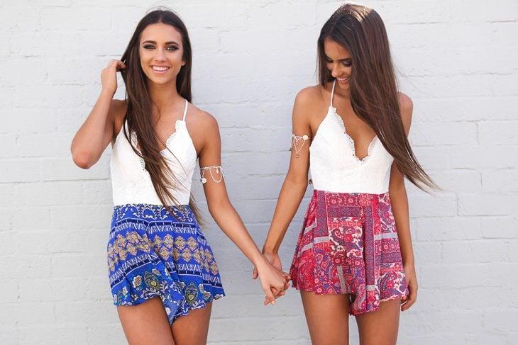 Mejores amigas tomadas de la mano vestidas de forma similar