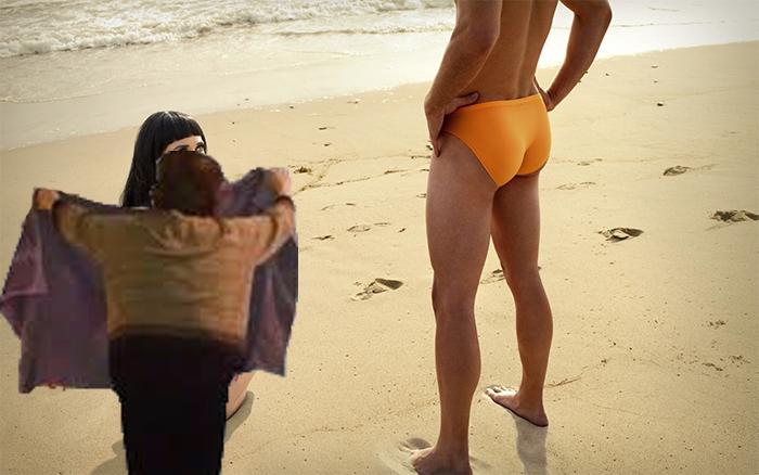 mujer tapa con toalla a mujer sentada en la playa con hombre enfrente