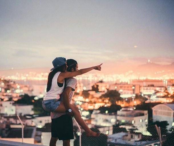Chica sobre la espalda de un chico ambos viendo el horizonte
