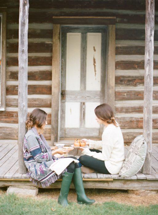 Chicas sentadas en un porche conversando mientras comen y toman té