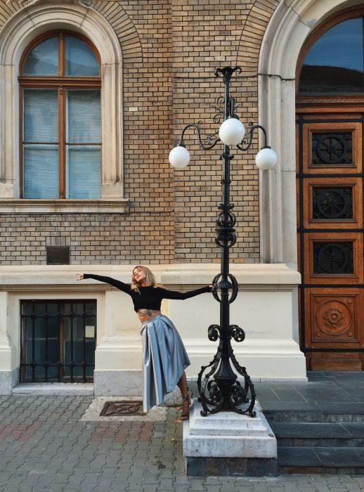 Chica bailando en la calle mientras se sostiene de un poste de luz