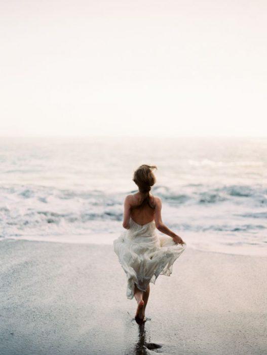 Chica corriendo por la playa hacia el mar