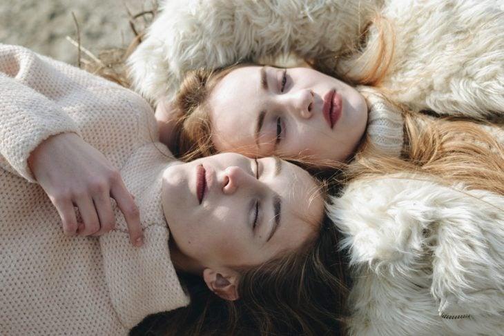 Chicas recostadas con su cara frente a frente