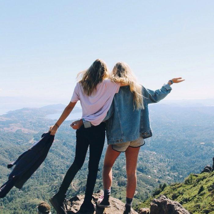 Chicas paradas sobre una montaña viendo hacia el vacío