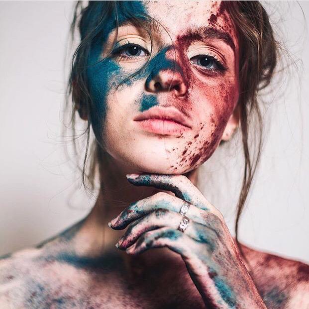 Chica con las manos y el rostro llenos de pintura