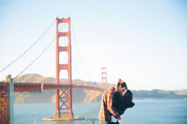 pareja abrazando y besandose en puente de sanfrancisco