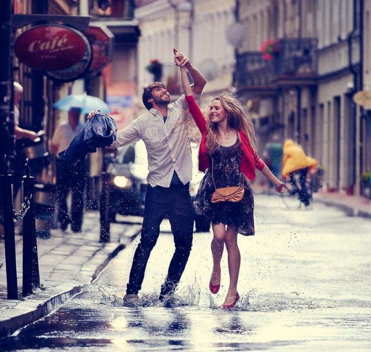pareja en la lluvia bailando y sonriendo