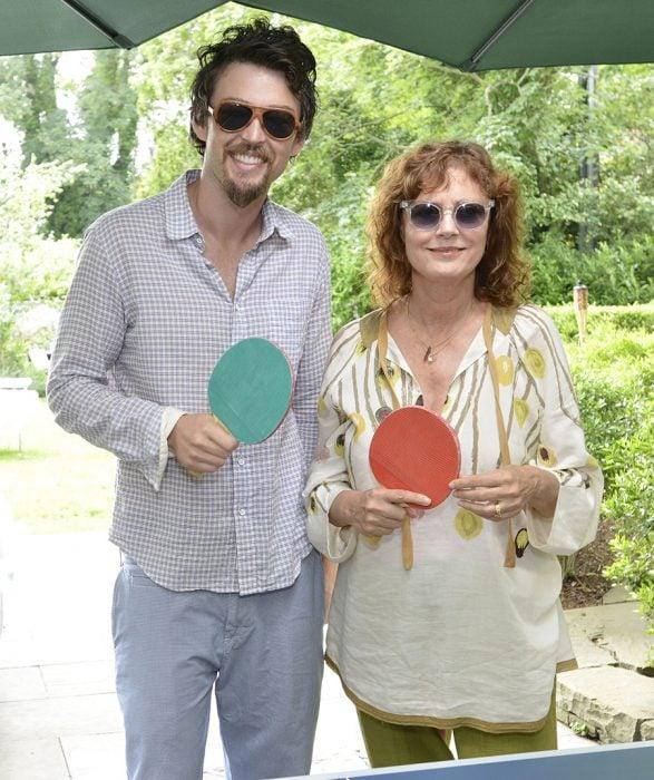 mujer con lentes y raquetas de ping pong y hombre a un lado
