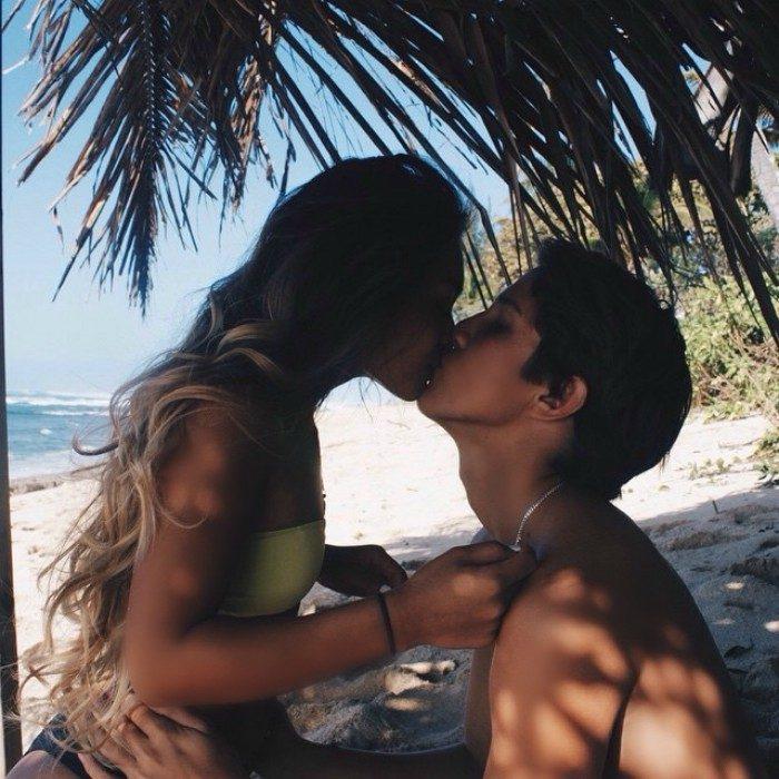 mujer besando a hombre en la playa